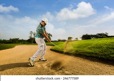 Golfer hitting the ball on the sand. Speeds Cause blurred by movement