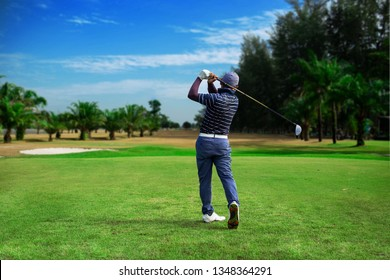 Golfer hitting golf shot with club on course vintage color tone, Man playing golf on a golf course in the sun, Golfers hit sweeping golf course in the summer