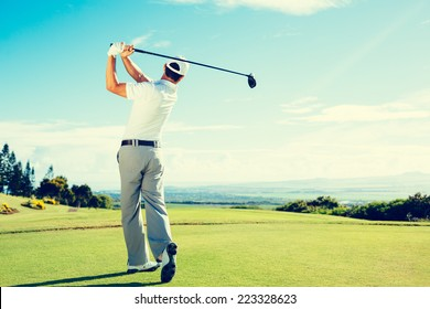Golfer Hitting Golf Shot with Club on Beautiful Golf Course on Vacation