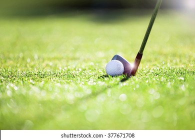 Golfer hitting iron club on golf course on fairway.