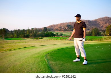 Golfer holding club in hands on green