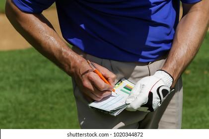 Golfer keeping score on scorecard