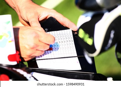 Golfer keeping scores in score sheet with hands
