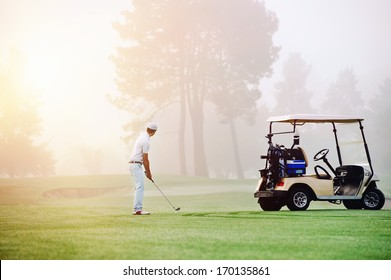 Golfer lining up shot with iron club on golf course in fairway at sunrise