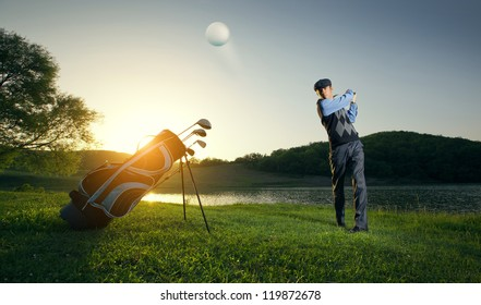 golfer makes a stroke at the ball