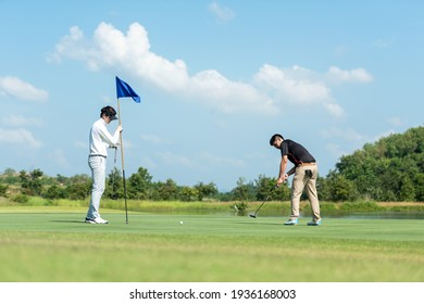 Golfer man and friend playing golf aiming shot for putting ball on the hole with club on green course.  Professional people hobby in holiday and vacations in sunny morning day on club golf.