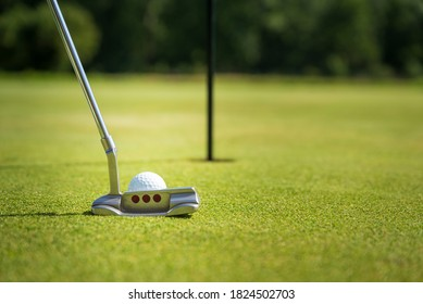 golfer near hole with ball and putter