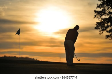 golfer on green backlit sunset