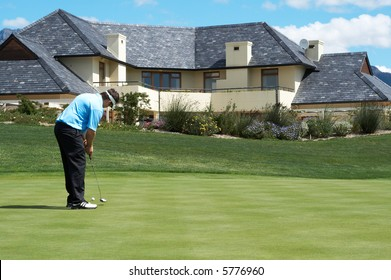 Golfer on the putting green next to a luxurious house