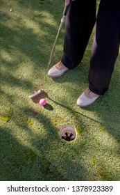 golfer on putting green with putter and golf ball