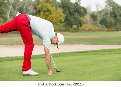 Golfer picking the ball from hole after successful put