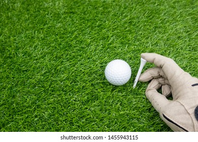Golfer is pinning the tee on green grass with golf ball on green grass.