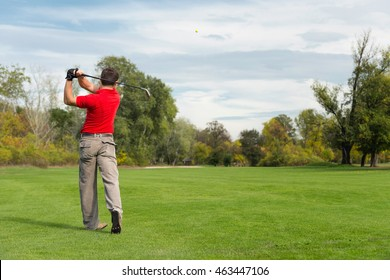 Golfer playing from fairway on a long hole, golf ball visible in the air