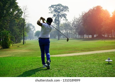 Golfer playing golf in the evening golf course, on sun set evening time. Man playing golf on a golf course in the sun.