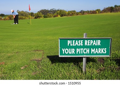 A golfer playing golf on a green.  Shallow D.O.F - sign in focus, golfer out of focus.