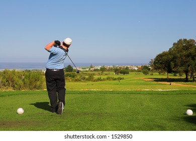 A golfer playing golf on a green.  Movement on golf club and ball in the air.