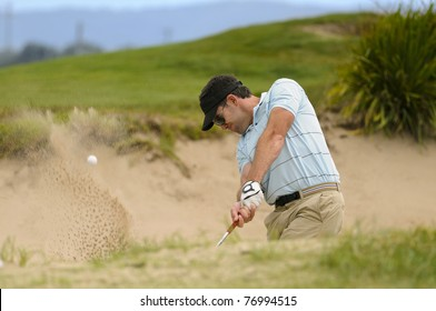Golfer plays a sand trap shot during his round