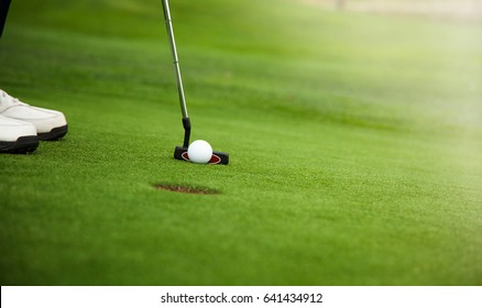 Golfer preparing for a putt on the green during golf course.