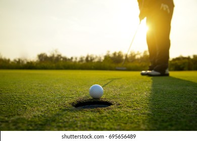 Golfer putt ball to hole on green golf course, sunset scene background with copy space on Left side.