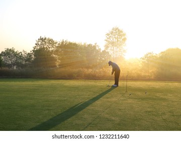 Golfer putting golf ball on the green , morning time