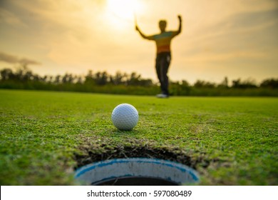 golfer putting golf ball on sunset time