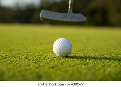 golfer putting golf ball on sunset time