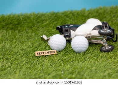 Golfer save the date in September with golf ball and golf bag on green grass
