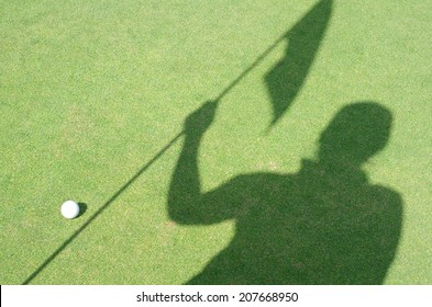 Golfer shadow hold flag on green golf