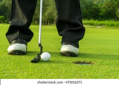 Golfer short putting golf ball on the green golf.