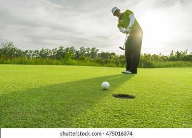 Golfer short putting golf ball on the green golf. morning time. copy space on Left side.