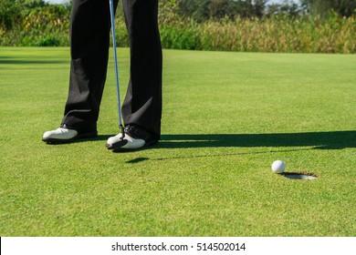 Golfer short putting golf ball to hole.