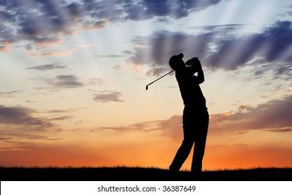 Golfer silhouetted against beautiful sunrise