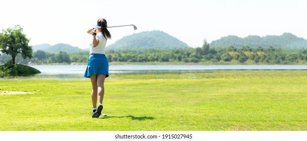 Golfer sport course golf ball fairway. People lifestyle woman playing game golf and hitting go on green grass river and mountain background.  Asia female player game shot in summer. copy space banner