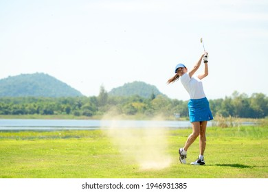 Golfer sport course golf ball fairway. People lifestyle woman playing game golf and hitting out of sand trap go on green grass. Asian female player game shot in summer. Healthy and Sport outdoor
