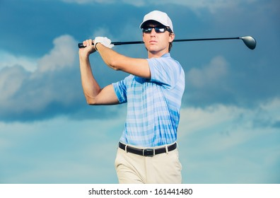 Golfer at sunset, Man swinging golf club with dramatic blue sky