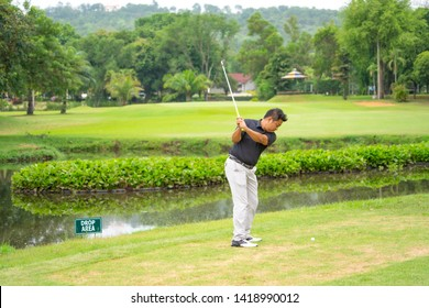 Golfer swing hitting golf ball in meadow course on summer holiday, player plyaing on drop area for hitting ball over river to green fairway.