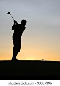 Golfer swinging his driver at sunrise.