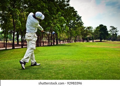 Golfer swinging his golf club and hit the golf ball from tee along the pretty green fairway on beautiful golf course