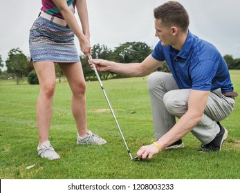 Golfer teaching his girlfriend how to play golf, lifestyle concept.