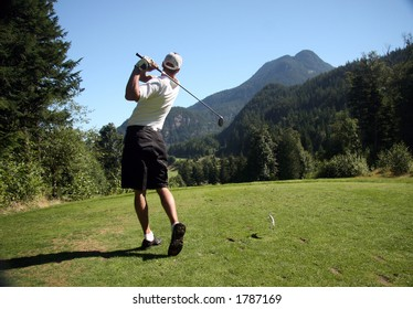 Golfer tees off on mountain course