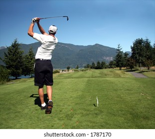 Golfer tees off towards ocean green