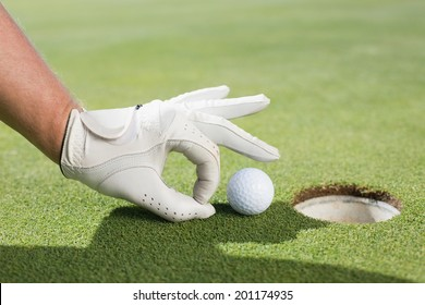 Golfer trying to flick ball into hole on a sunny day at the golf course