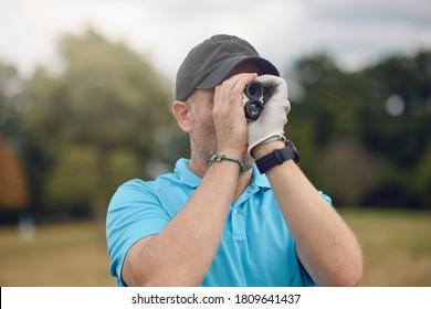 Golfer mit einem Rängefinder, um die Entfernung zu dem Loch zu messen, das es zu seinem Auge hält, während er sich in einer Nahaufnahme auf dem Fairway in einem gesunden aktiven Lifestyle- oder Sportkonzept herunter dreht