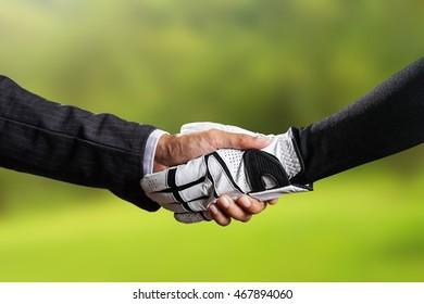 Golfer Wearing Golf Glove shake hand with businessman on golf course blur background