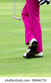 golfer wearing pink slacks and white shoes