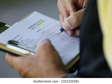 a golfer writes on his scorecard during a golf tournament