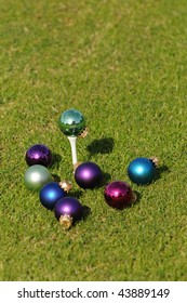 Golfer's Christmas with assortment of ornaments surrounding and on a Golf Tee.  Focus is on the ornament on the golf tee.