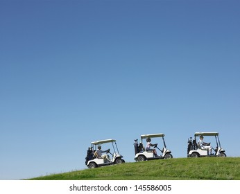 Golfers driving carts in a row against clear blue sky