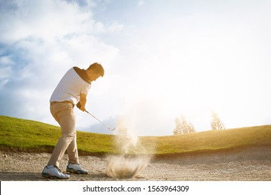 Golfers exploding sand in the bunker.