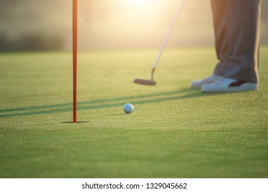 Golfer's feet who are putting golf balls on the green in the warm sunshine in the morning.
